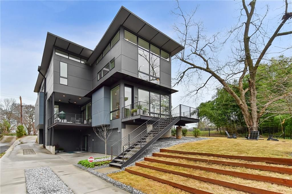 A large grey modern home with a big deck.
