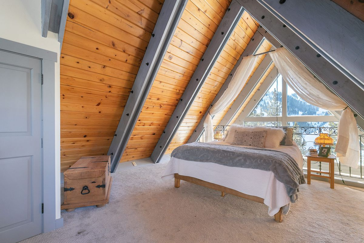 A bed sits underneath the loft section of an A-frame house.
