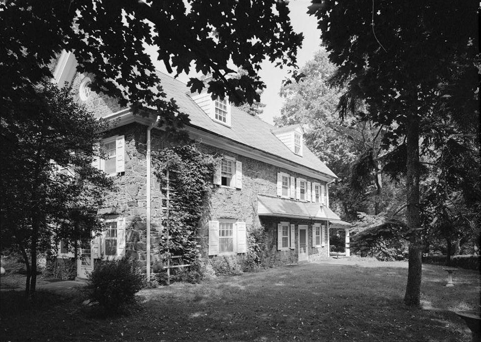 The exterior of Wynnestay in Philadelphia. The farmhouse has a stone facade and is surrounded by trees.