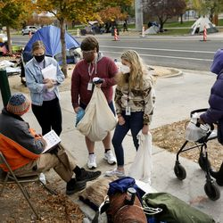 The Road Home's Marissa Beckstrom, Zachery Davis and Claudia Payor speak to homeless veteran Michael Standish about housing options at Taufer Park in Salt Lake City on Friday, Oct. 23, 2020.