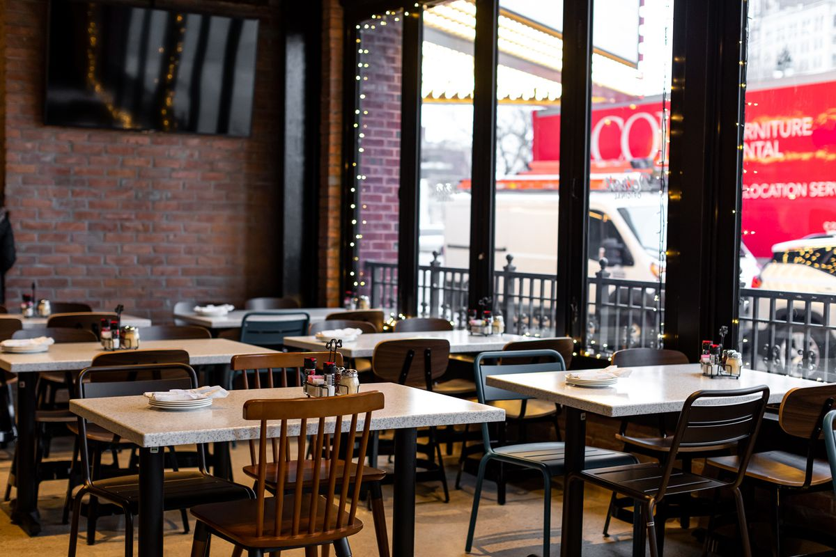 Mismatched chairs surround white four-top tables near the windows at Buddy's in downtown Detroit.