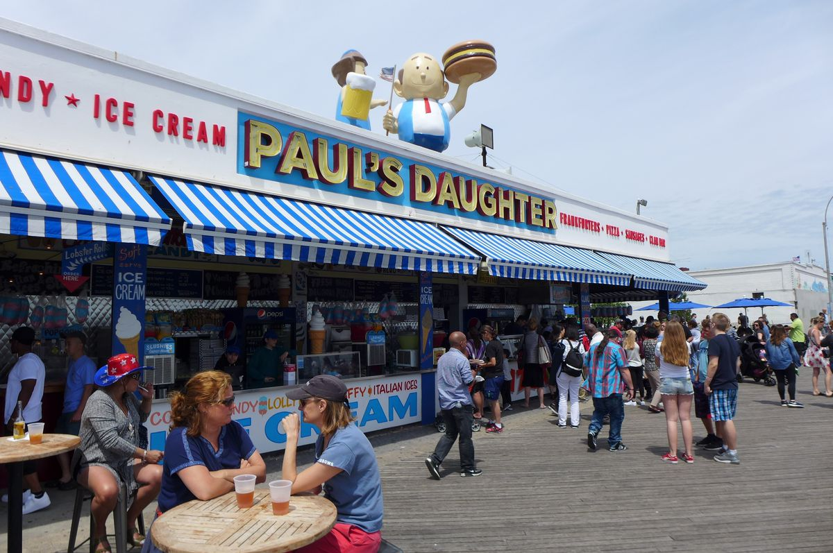 A broad storefront on the boardwalk with a figure on top holding a hamburger aloft.