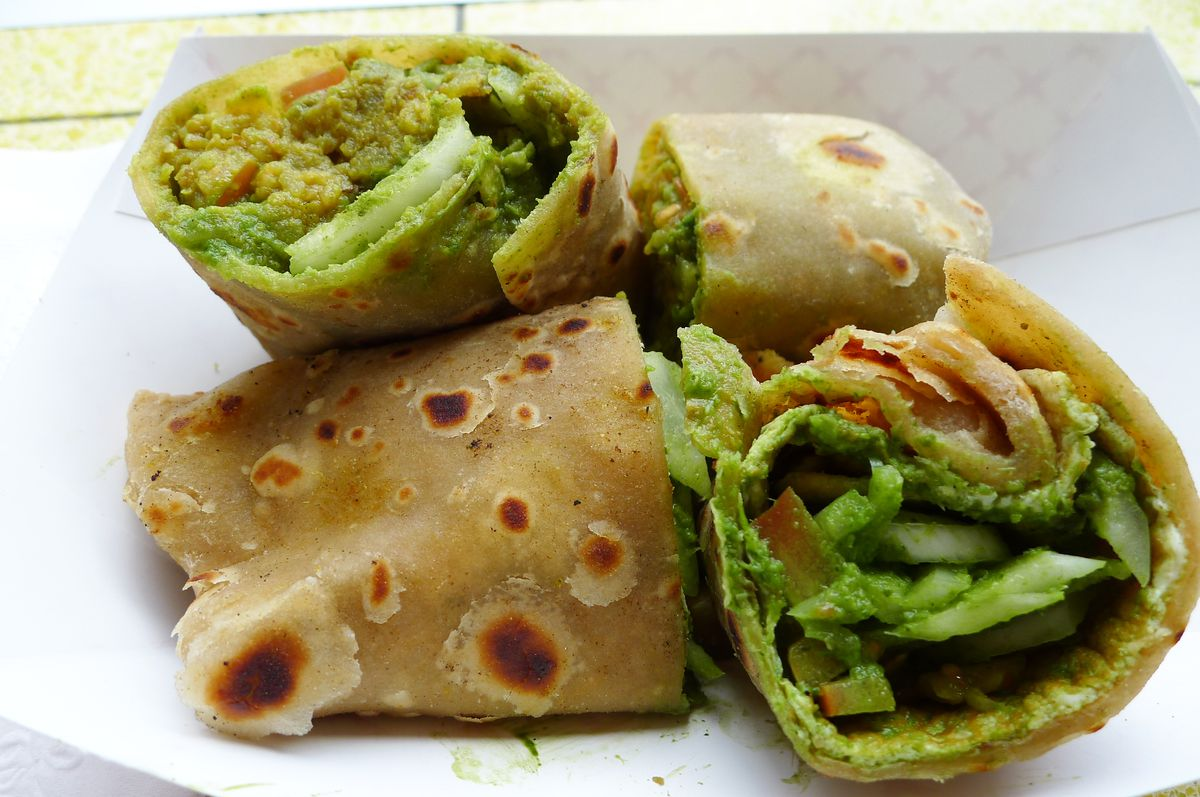 A roti roll from Bombay Frankie cut into three pieces to show its vegetable laden interior.