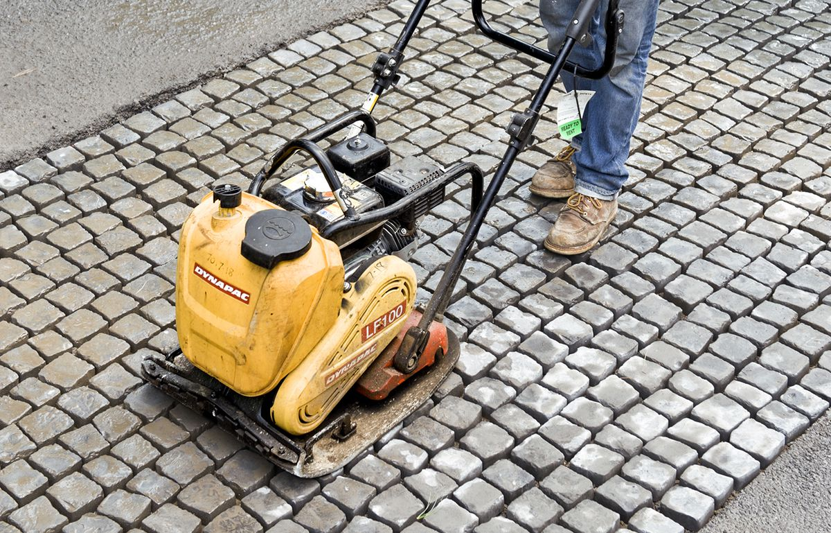 Man Compacts Cobbles With Plate Compactor Over Surface