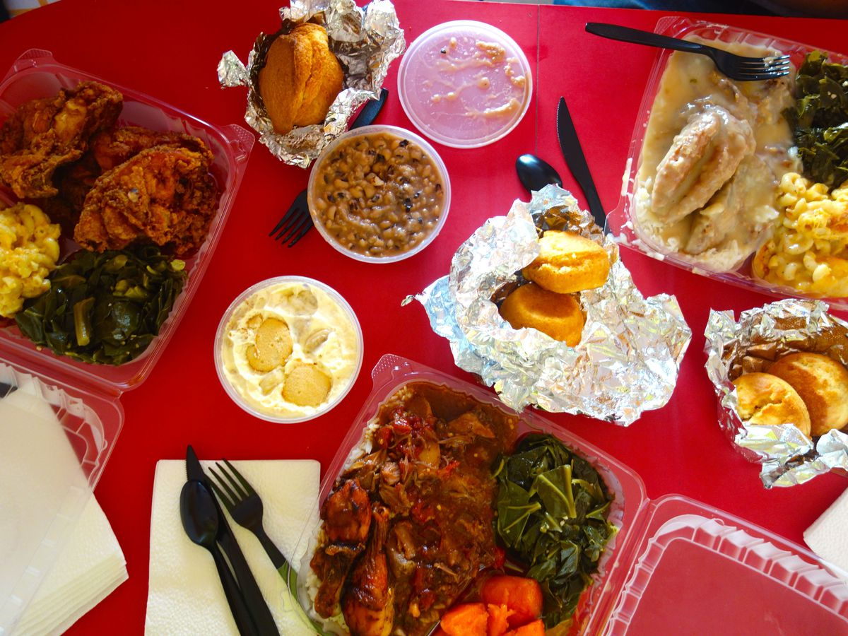 A spread of meals at Lena's, each packed in a plastic container, with cornbread wrapped in foil