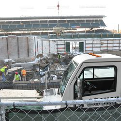 Along the wall, a bucket of concrete is being lowered by a crane in right field