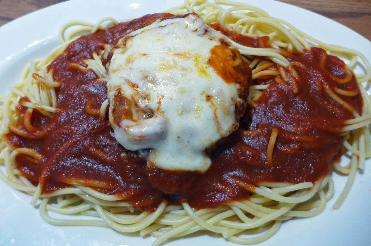Chicken parm is served over spaghetti.