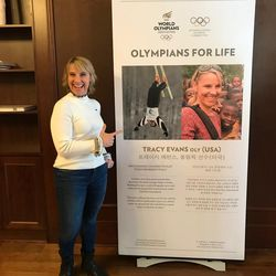 Park City resident and three-time aerial Olympian Tracy Evans poses with a poster displayed at a ceremony honoring her and four other former Olympians for their humanitarian efforts.