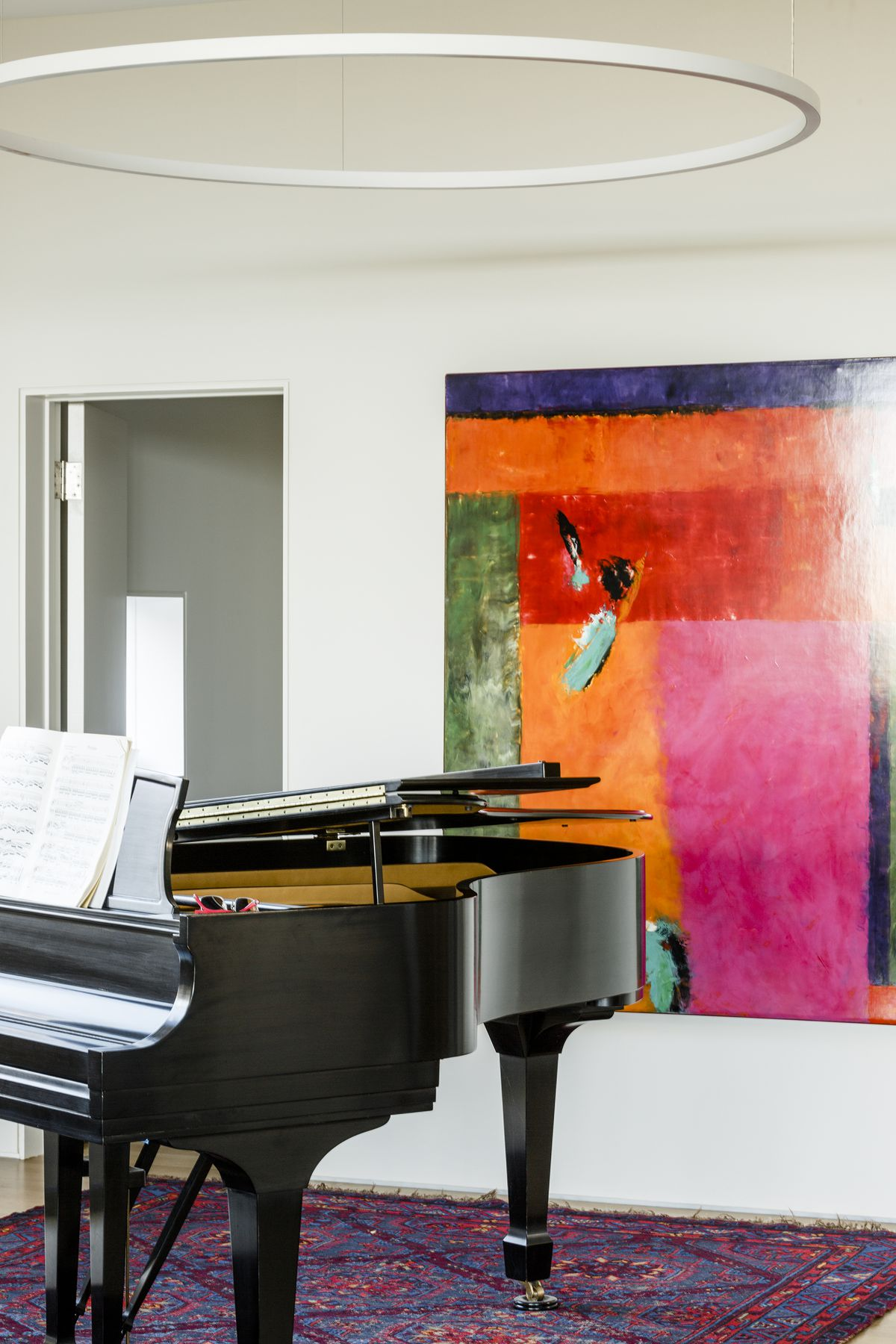 A large, black piano sits on a rug and hardwood floor. It's topped by a large, hoop-like light fixture. A brightly colored painting (mostly orange, red, and pink) hangs behind it.