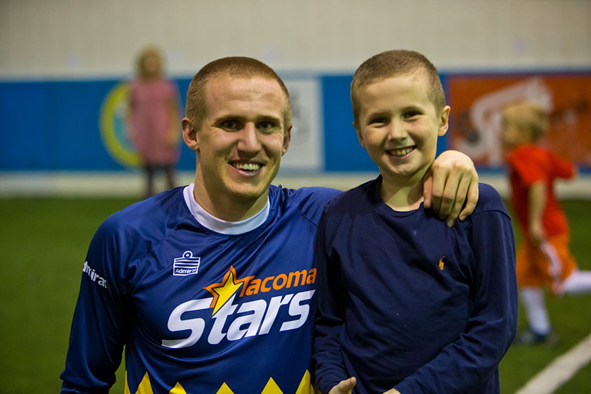 Phillips takes time to pose with a fan after his final game at Tacoma Soccer Center.