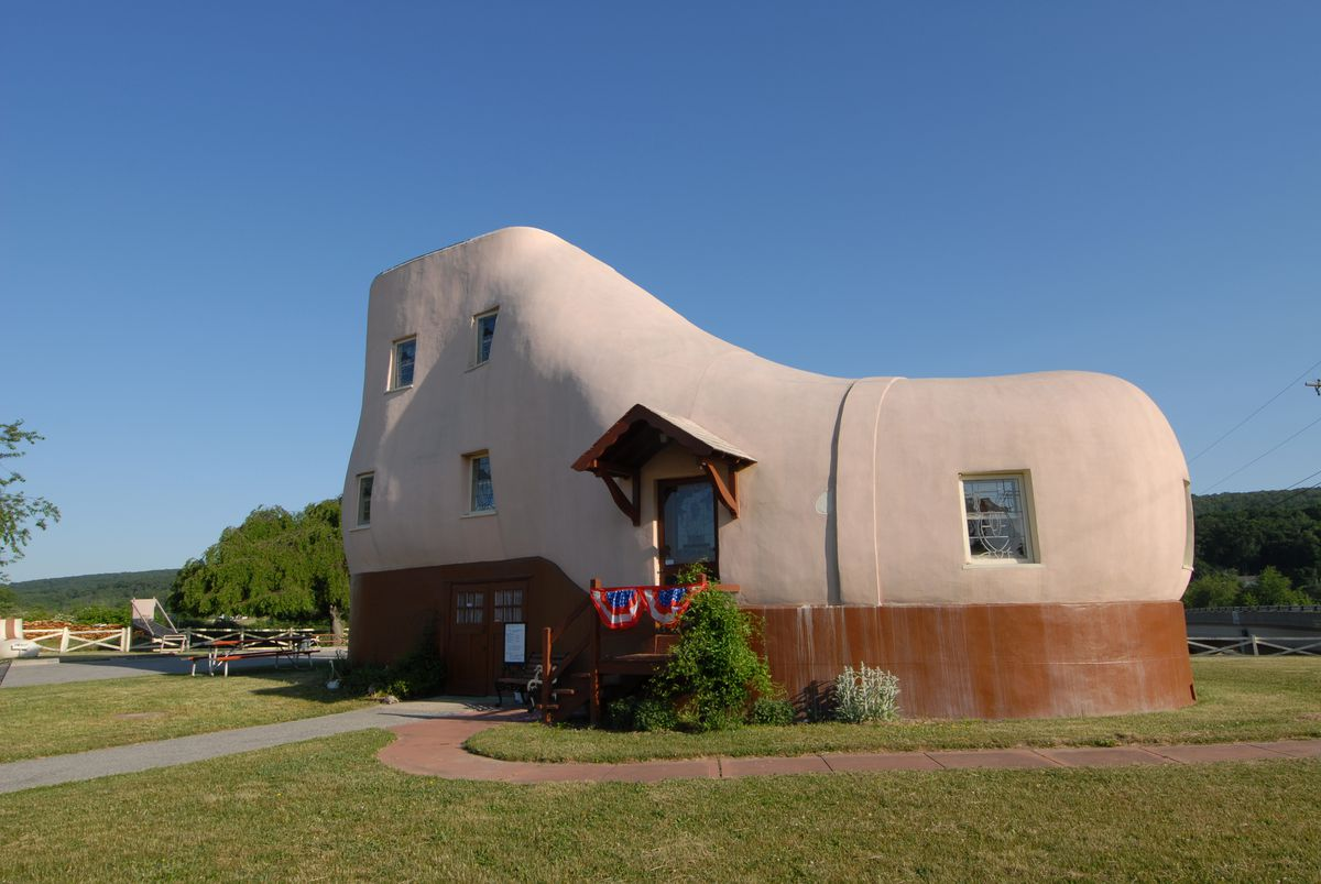 A house shaped like a shoe in Hellam Township, Pennsylvania. The house is tan and brown with multiple windows. There is a path leading to the front entrance and a lawn in front.
