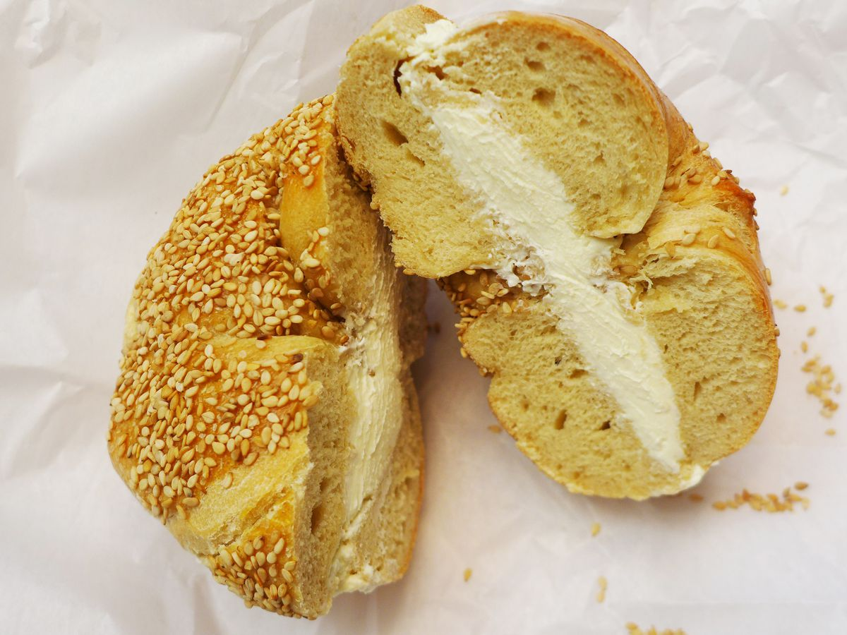 A seeded bagel cut open and smeared with white cream cheese.