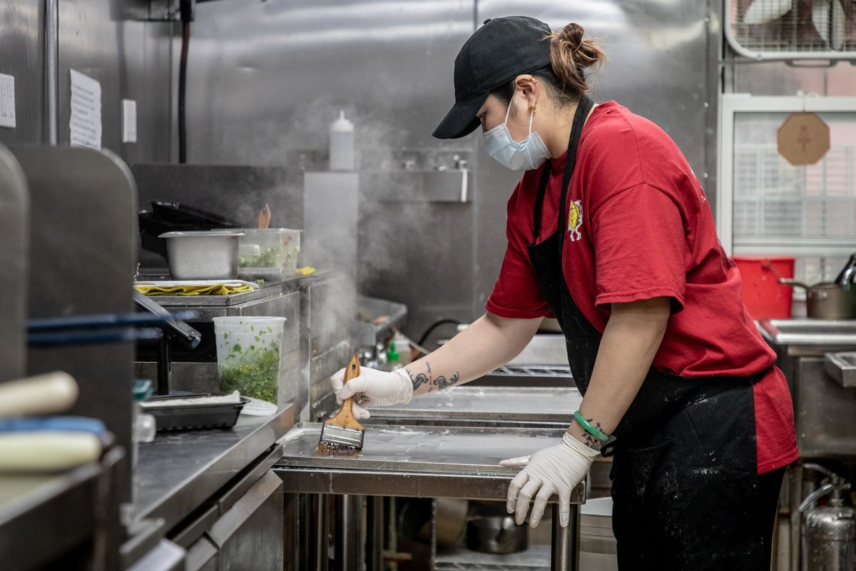 A woman wearing a face mask, red t-shirt, black baseball cap, and black apron, brushes oil onto a restaurant grill as steam rises in the background.