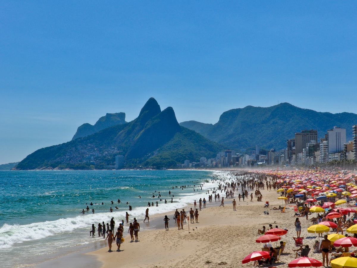 An aerial view of Praia de Ipanema in Rio de Janeiro, Brazil. In the foreground is a sandy beach with colorful umbrellas and beachgoers. In the distance are mountains.
