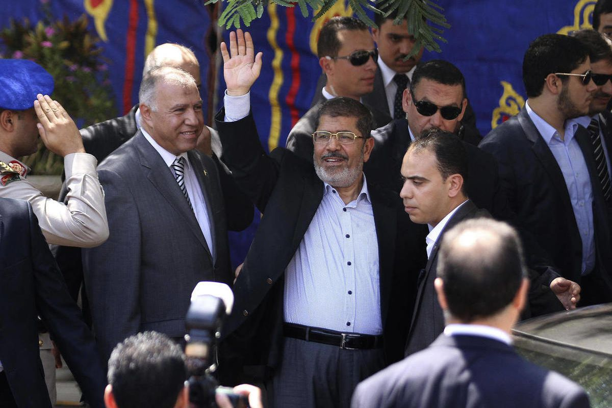 Egyptian President Mohammed Morsi, center, waves to worshippers ash he arrives for Friday prayers at Sayyeda Zainab mosque in Cairo, Egypt, Friday, Sept. 7, 2012.
