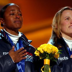 With tears and smiles, Vonetta Flowers, left, and Jill Bakken listen to the American national anthem during an awards ceremony at the Olympic Medals Plaza on Wednesday, Feb. 20, 2002.