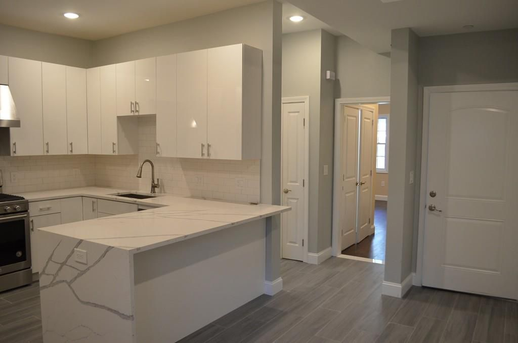 An open kitchen with a long, wrapping counter, and there's a short hallway showing that leads to other rooms.