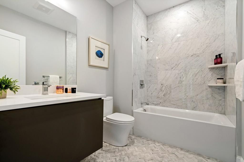 A bathroom with a vanity next to a toilet next to a shower without a curtain.