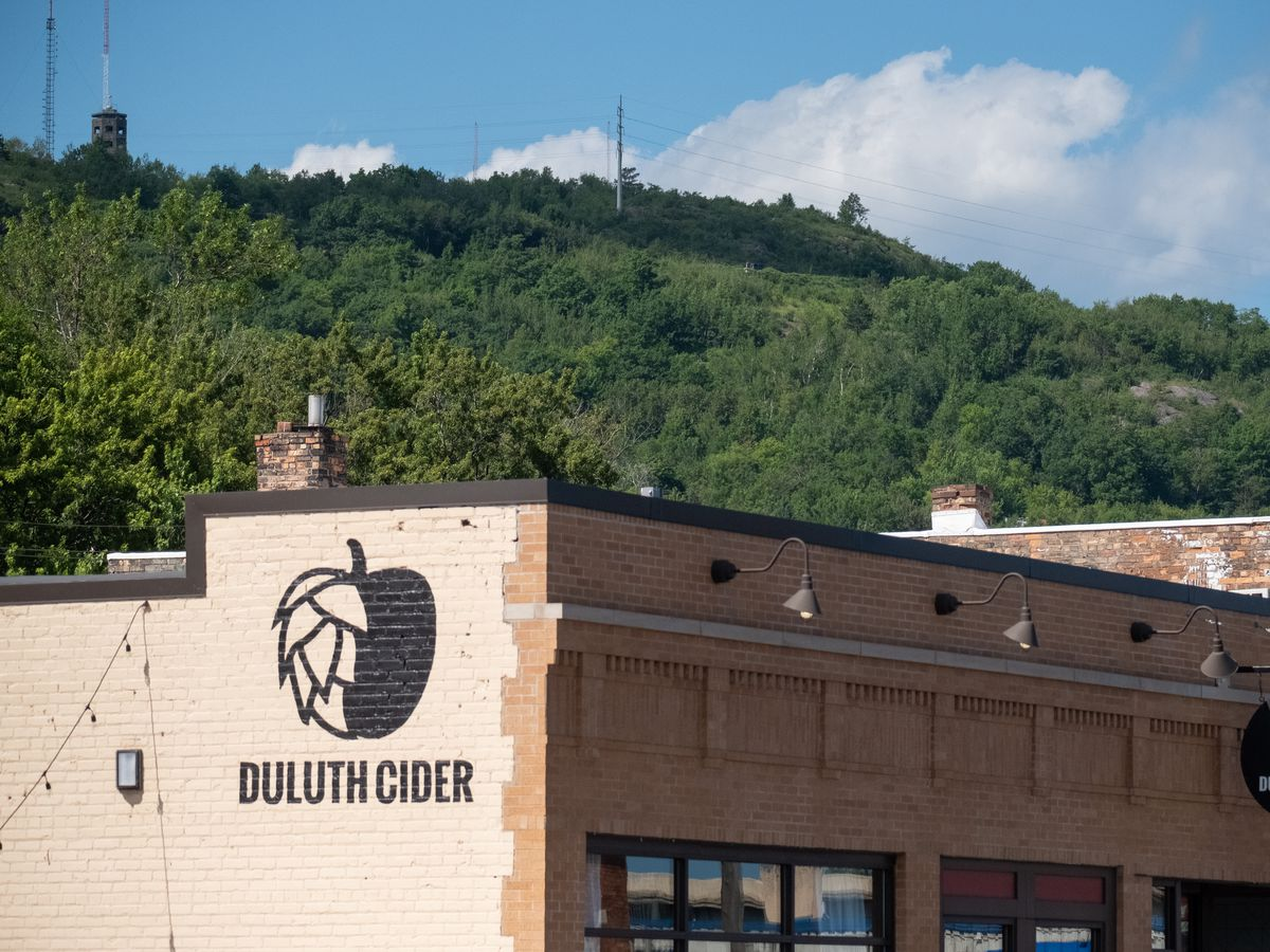 The top of the brick exterior of Duluth Cider with a view of Enger Tower and the hill in the background