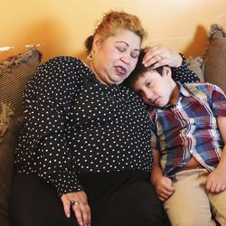 Lisia Gassant hugs son Marcus, 9, as they listen to the 190th Semiannual General Conference of The Church of Jesus Christ of Latter-day Saints from their home in West Valley City on Sunday, Oct. 4, 2020.