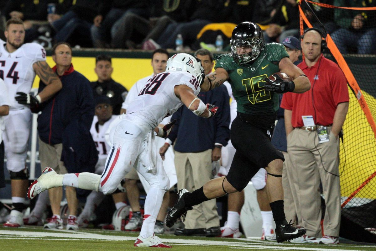 September 22, 2012; Eugene, OR, USA; Oregon Ducks tight end Colt Lyerla (15) stiff arms Arizona Wildcats safety Jared Tevis (38) as he runs with the ball along the sideline at Autzen Stadium. Mandatory Credit: Scott Olmos-US PRESSWIRE
