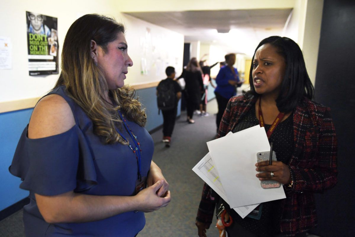 A teacher talks about one of her students with principal Biaze Houston, right, at East Middle School in Aurora. (Photo by Joe Amon/The Denver Post)