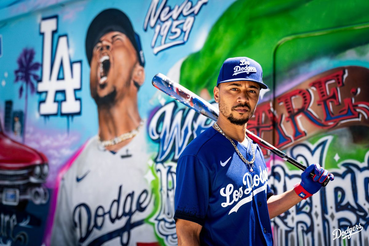 Mookie Betts models the Dodgers' City Connect jersey in front of a mural.