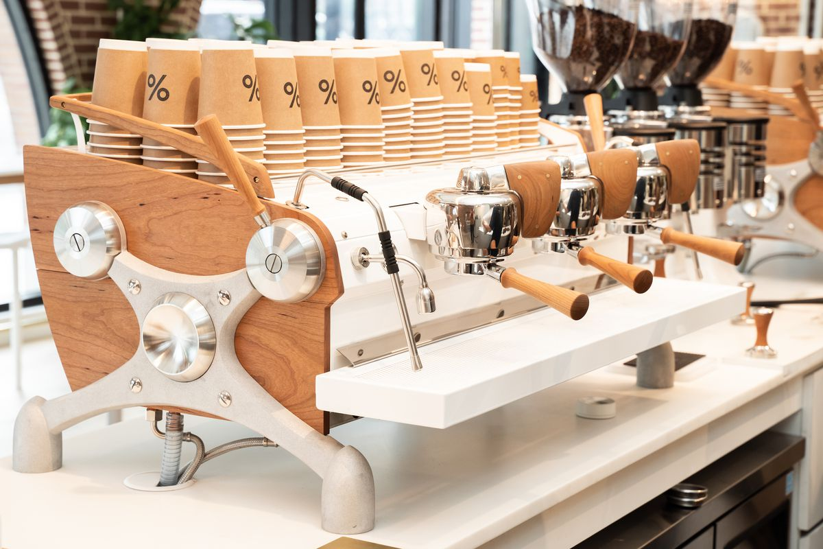 A light wood-accented espresso machine sitting on a white counter with paper coffee cups stacked on top of the machine