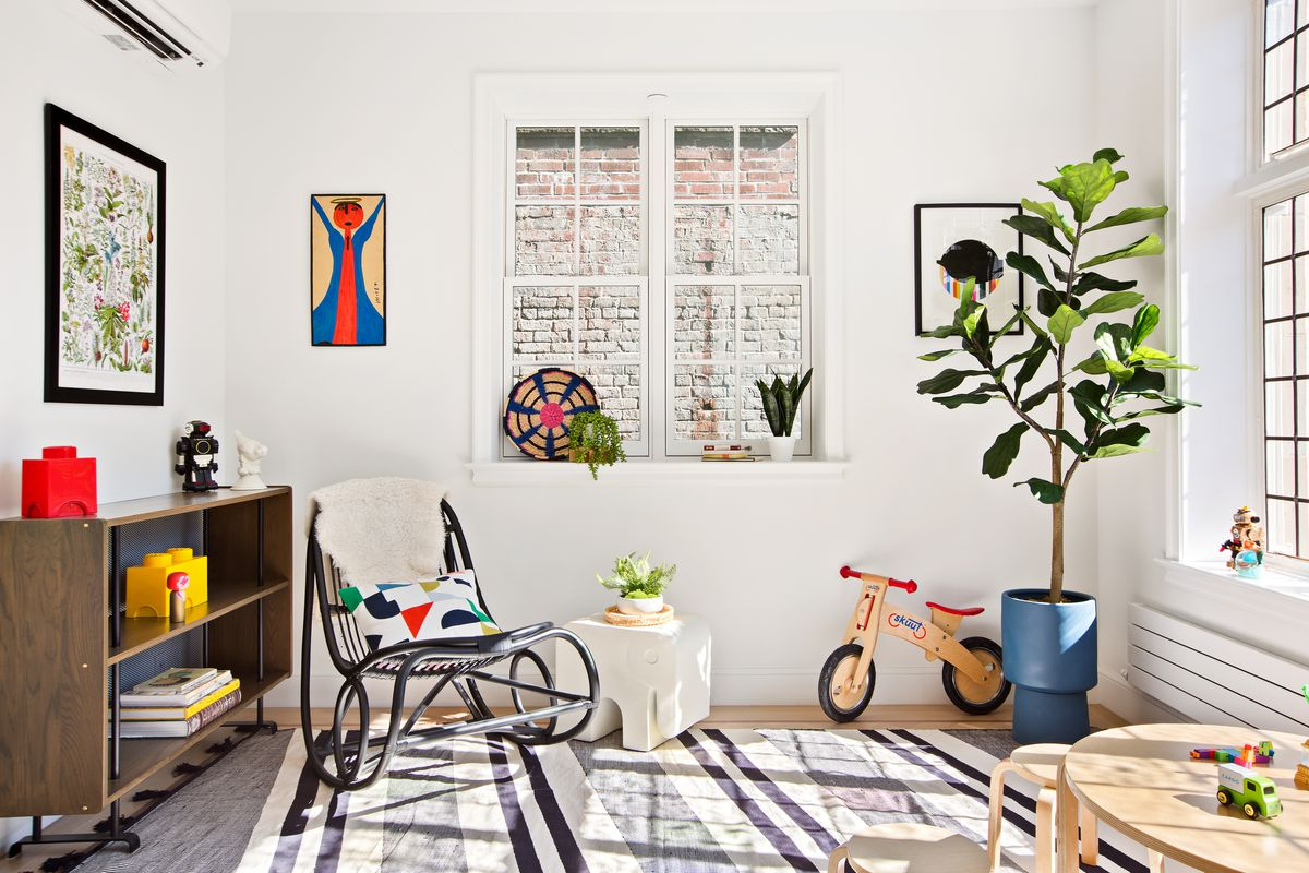 A small room with a planter, a rocking chair, a small wooden table, and toys.