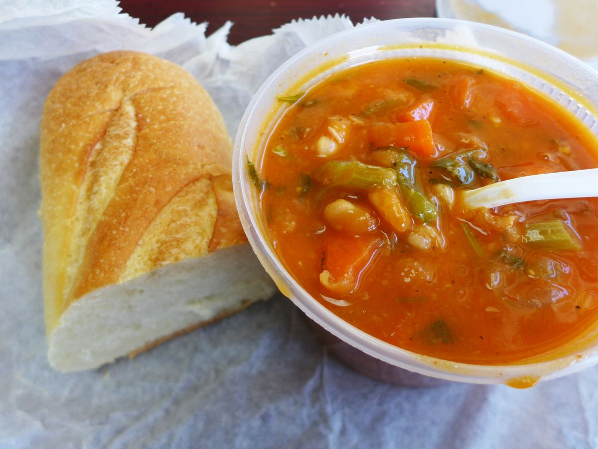 A bowl of vegetable soup with a loaf of bread on the side.