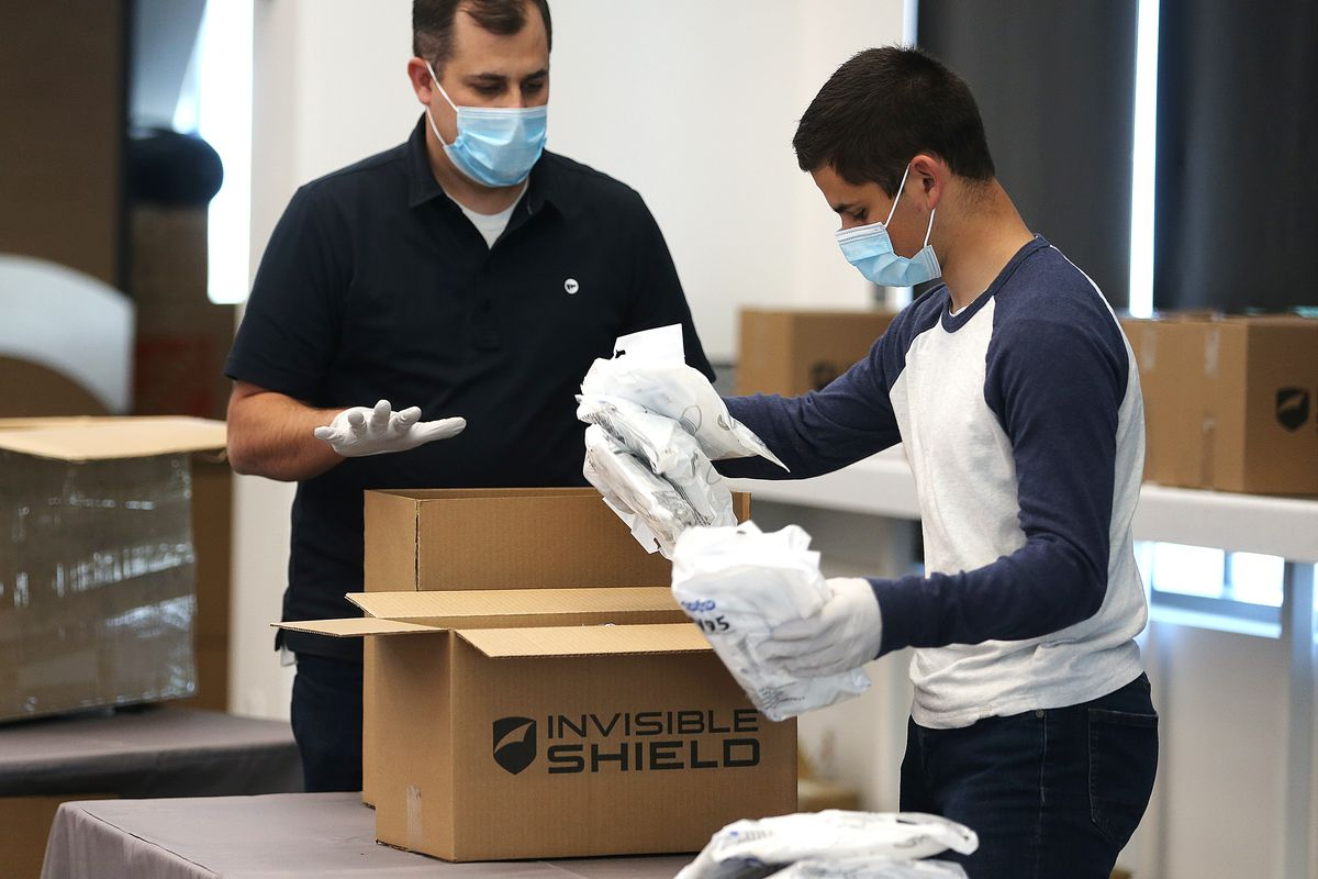Brad Bell and his son, Ryan Bell, pack N95 masks into boxes at Zagg headquarters in Midvale on Tuesday, April 14, 2020.The company is donating 10,000 of the masks to hospitals, medical professionals and high-risk individuals to help combat the spread of COVID-19 in the communities in which the company operates.