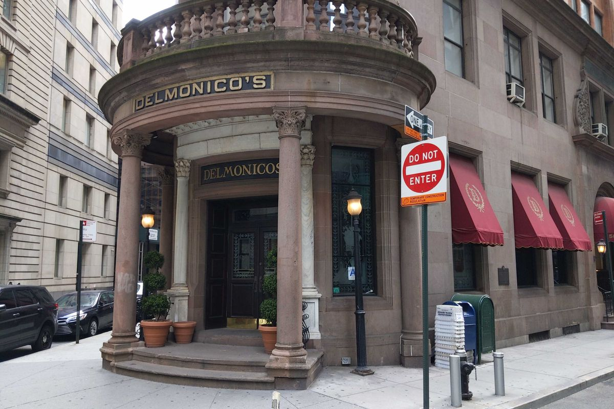 The exterior of a building with stone pillars and a sign that reads Delmonico's
