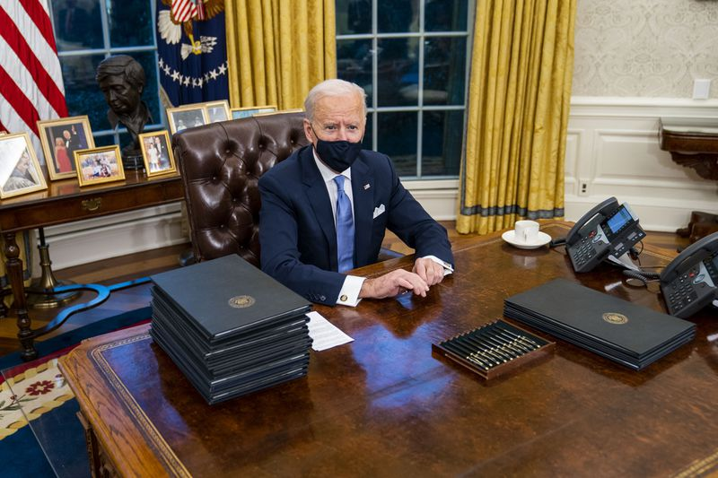 President Biden sitting at his desk in the Oval Office with a stack of executive orders ready to sign.