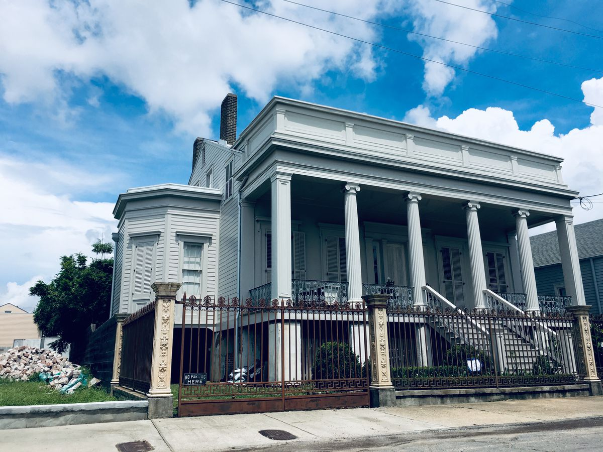 A creepy mansion with ionic columns and an iron fence
