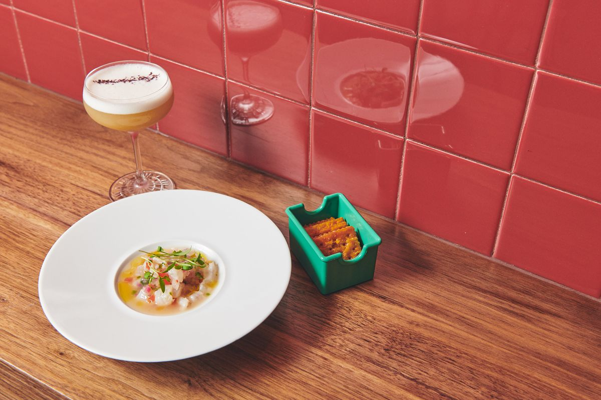 Fluke ceviche sits in a white bowl next to a teal cracker holder on a brown wooden counter