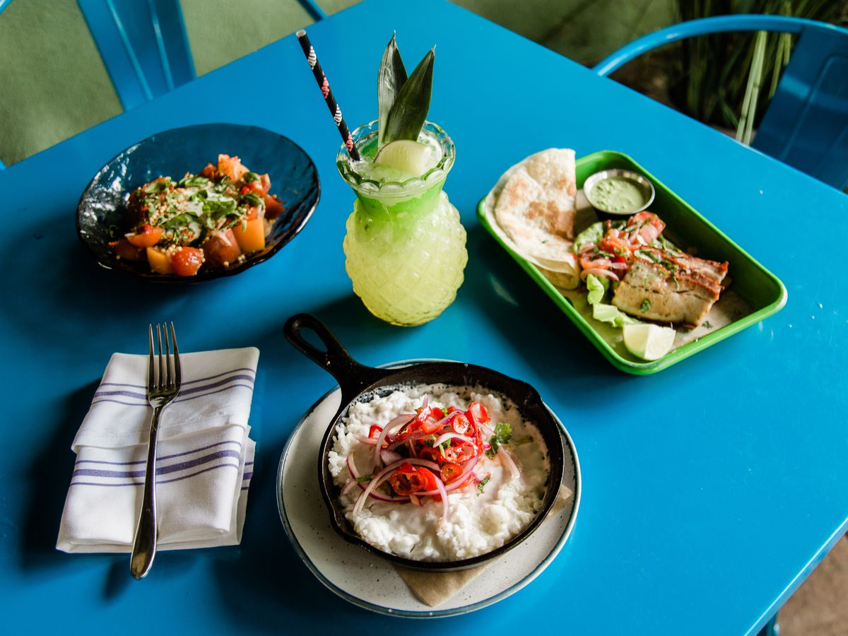 Coconut rice, pork belly taco, and a salad with a tropical cocktail
