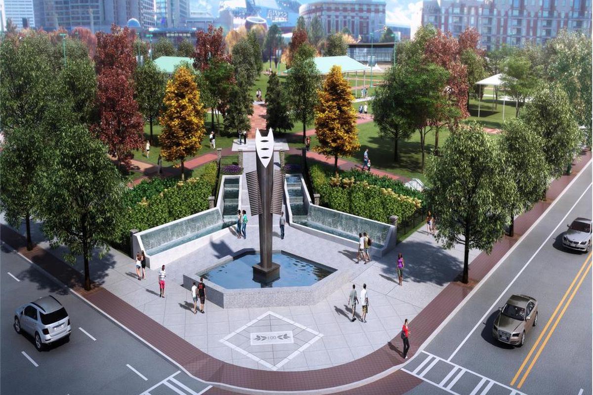 A large paved plaza with water feature and torch-like sculpture leads into the park.
