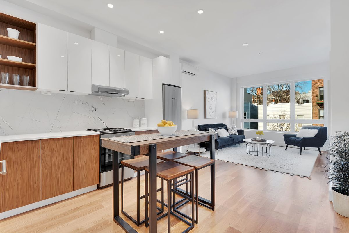A living area with hardwood floors, a large window, a wooden dining table, and a kitchen with white cabinetry.