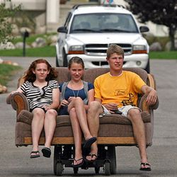 Nick Homer, right, takes his sister, Teresa Homer, center, and her friend, Elizabeth Christensen, out on his motorized couch.