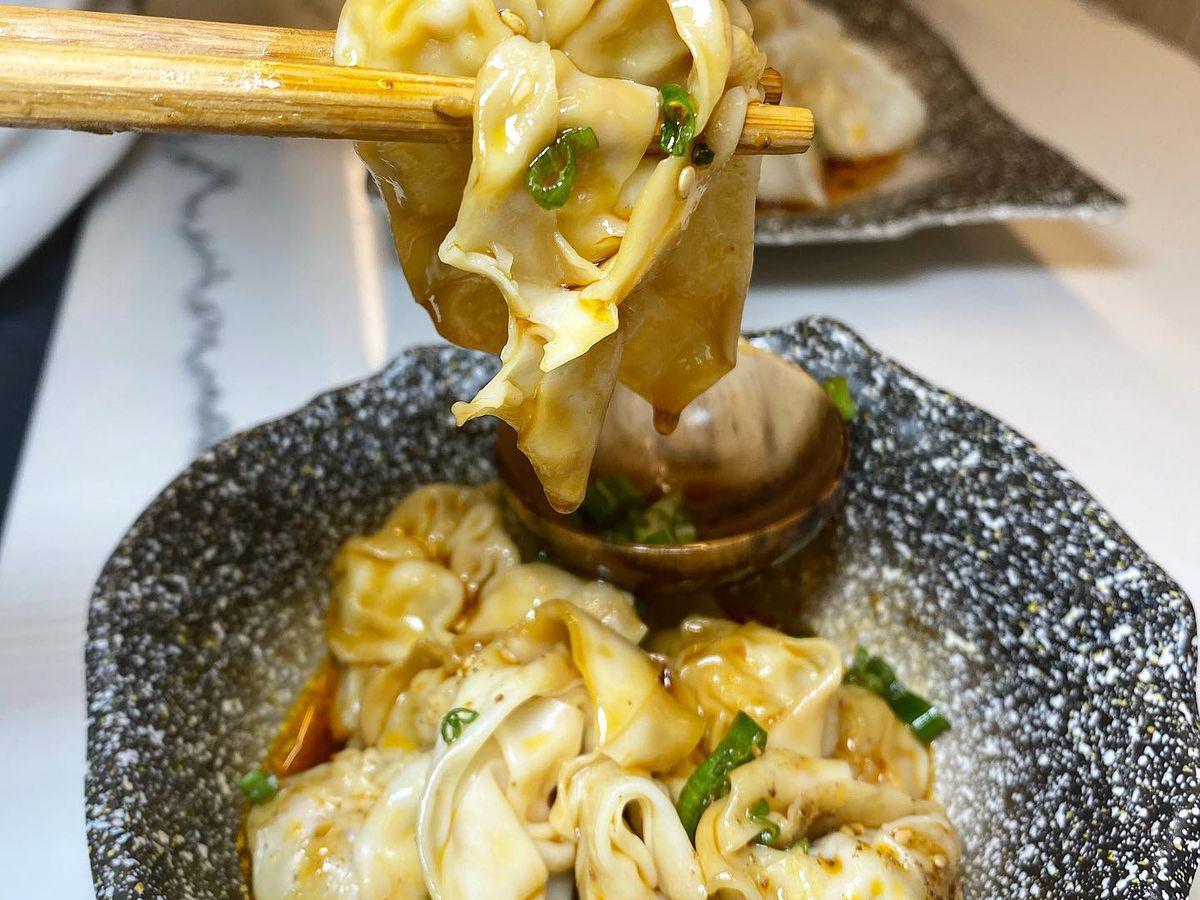 A pair of chopsticks hold a wonton over a bowl of wontons