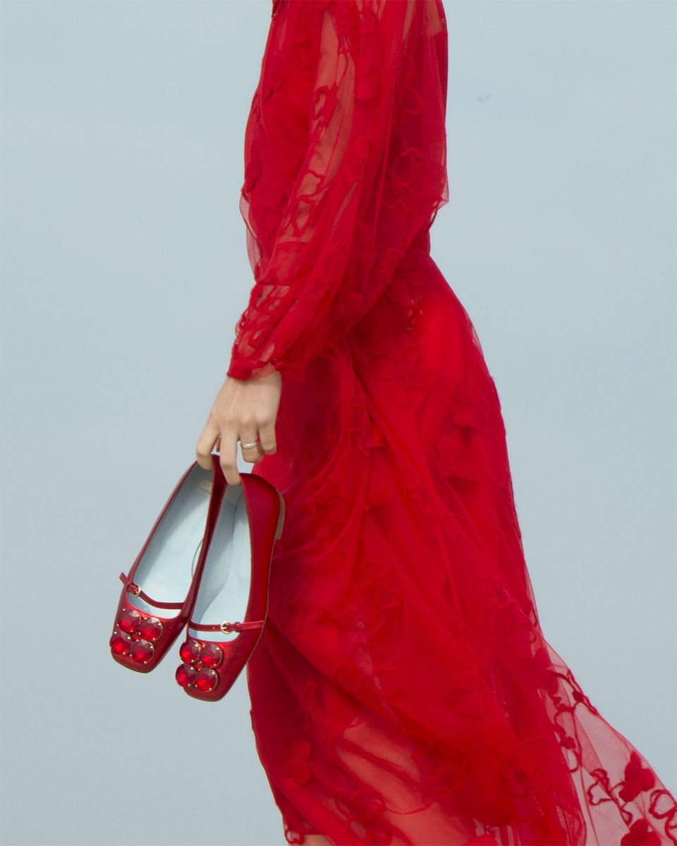 A woman in a red dress carries red embellished heels