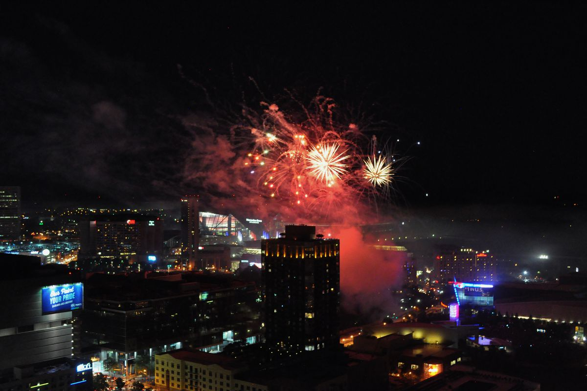 Red fireworks exploding over the park, with the two stadiums in the background, seen from above.