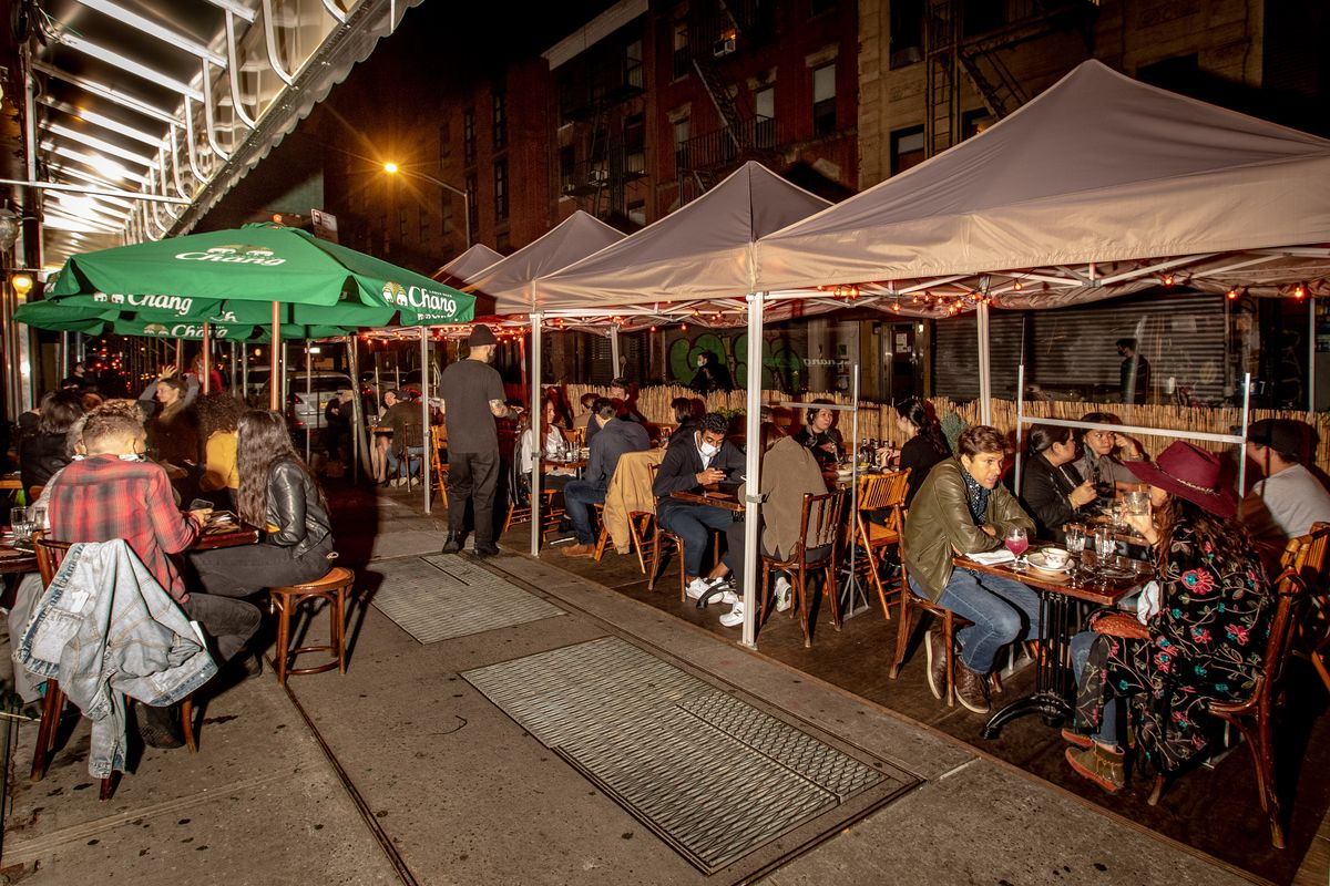 Patrons sit under a big white tent to the right, and green umbrellas to the left, in an outdoor dining setup