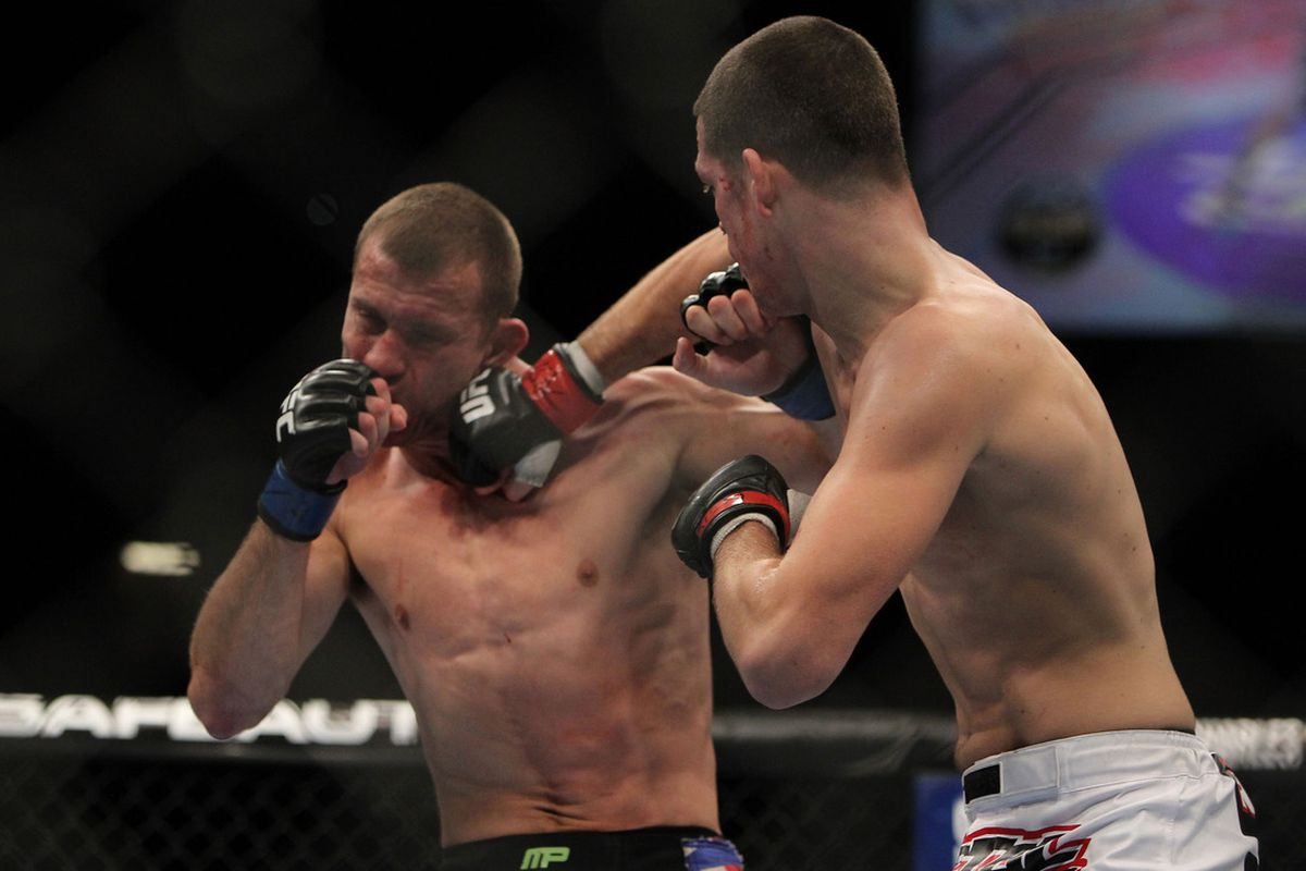 LAS VEGAS, NV - DECEMBER 30: Nate Diaz (right) punches Donald Cerrone (left) during the UFC 141 event at the MGM Grand Garden Arena on December 30, 2011 in Las Vegas, Nevada. (Photo by Josh Hedges/Zuffa LLC/Zuffa LLC via Getty Images)