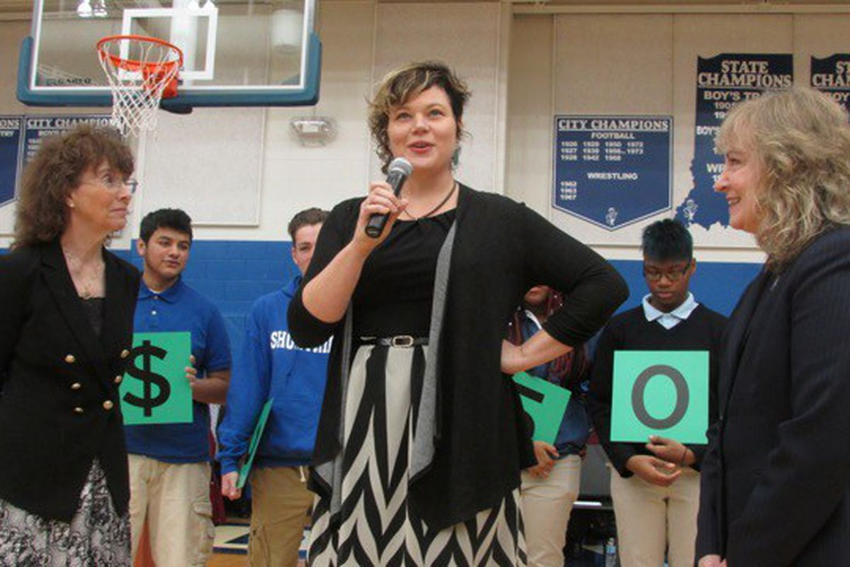 English teacher Melody Coryell speaks to Shortridge High School students after receiving the $25,000 Milken Award from Jane Foley, senior vice president of the Milken Educator Awards (left) and Indiana state Superintendent Glenda Ritz (right).