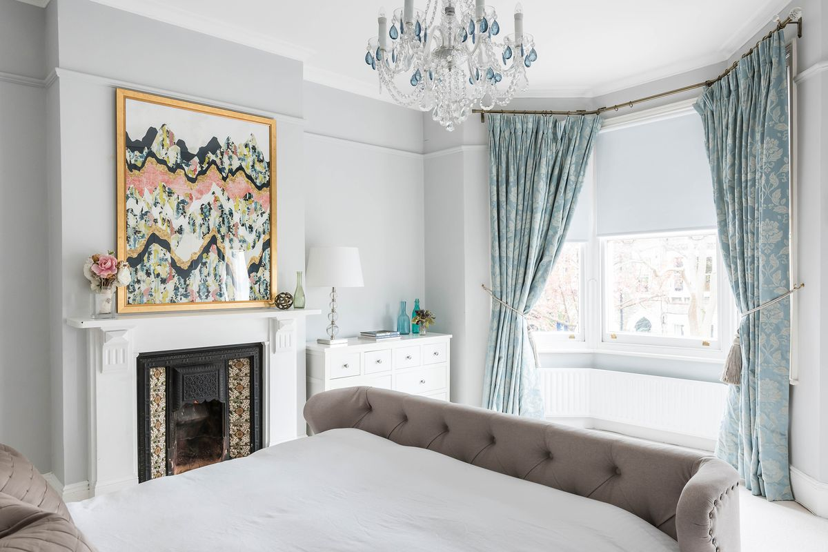 Bedroom with large painting about fireplace.