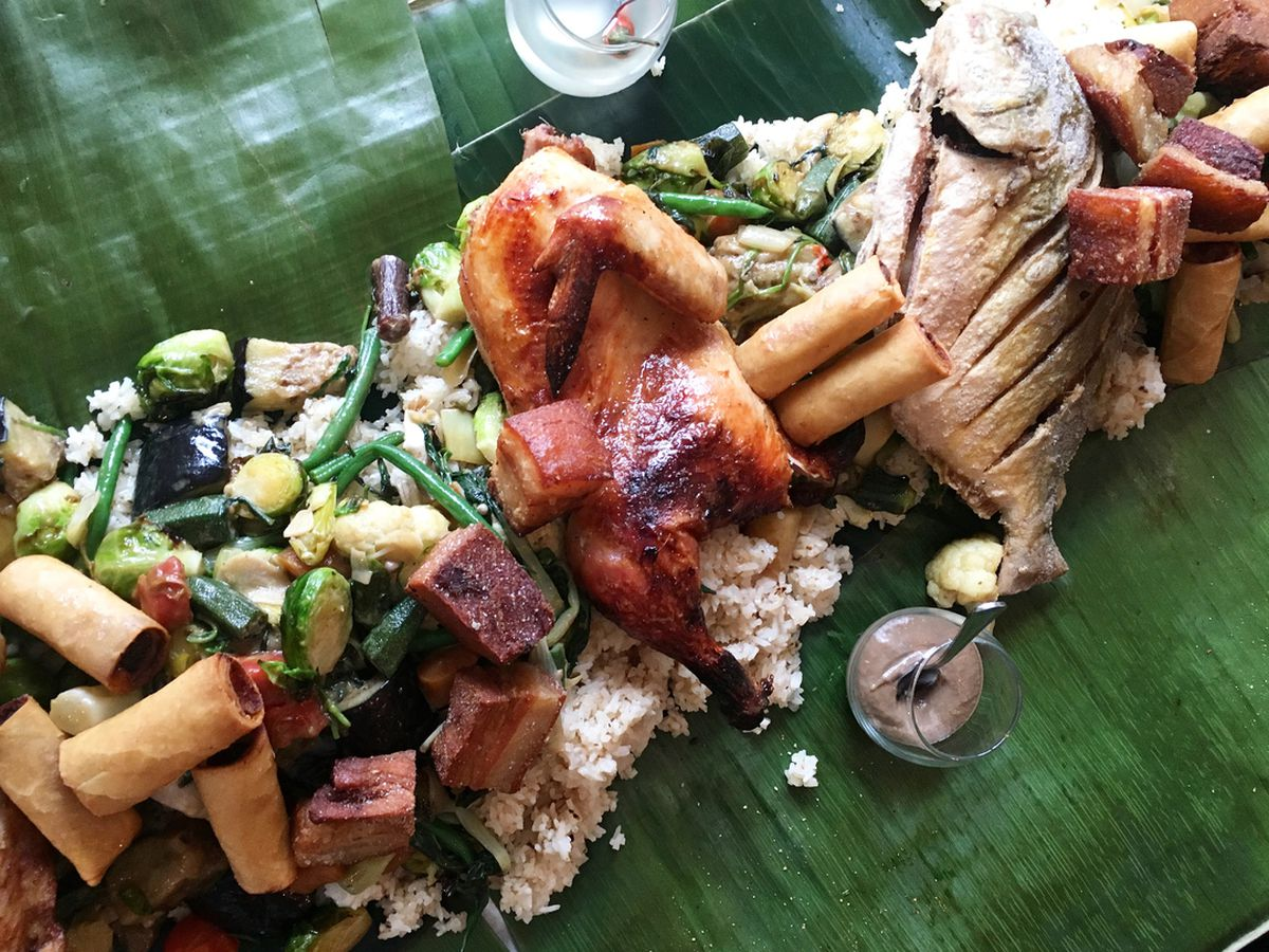 chicken, fish, and spring rolls piled on banana leaves