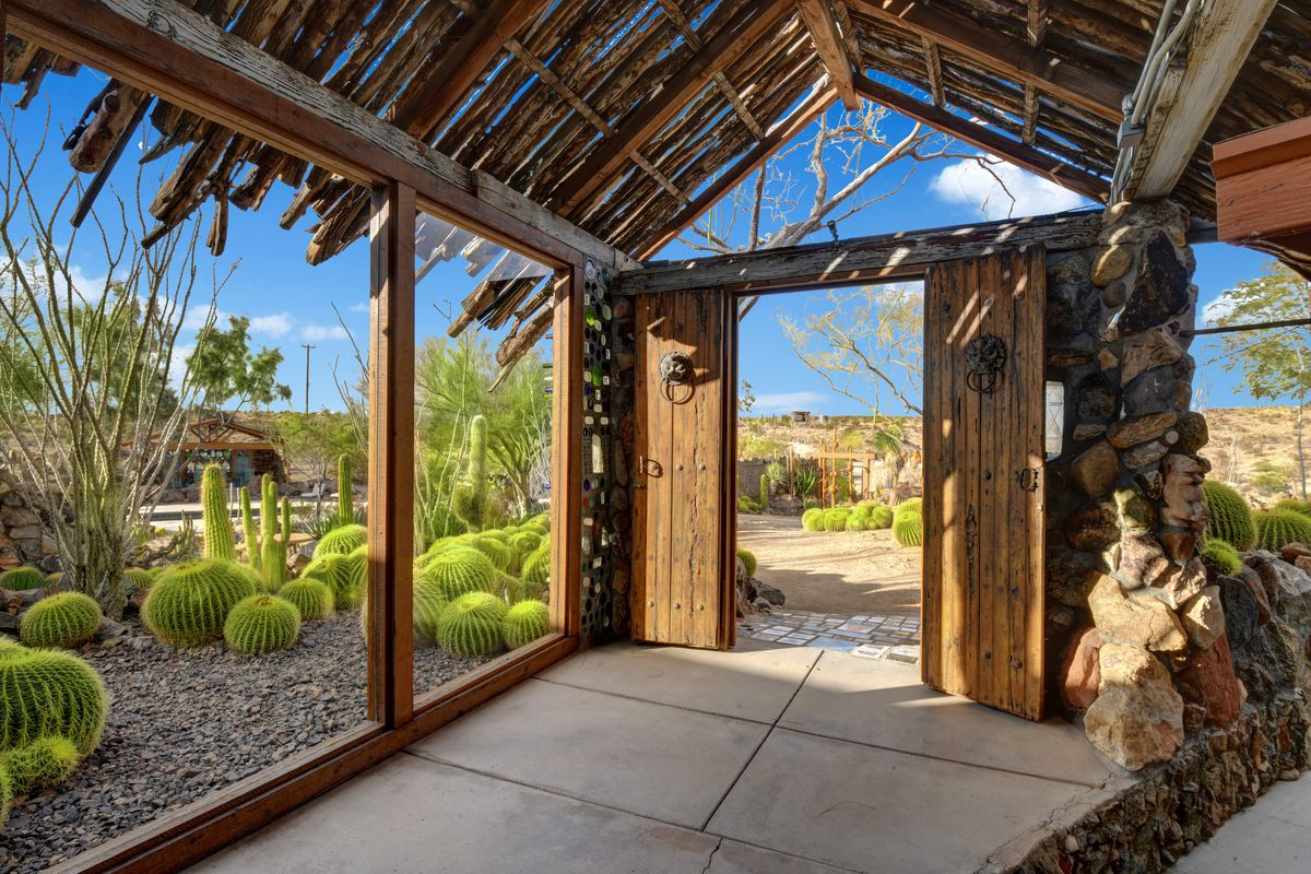 A hallway with rustic wood and glass looking out to the desert.