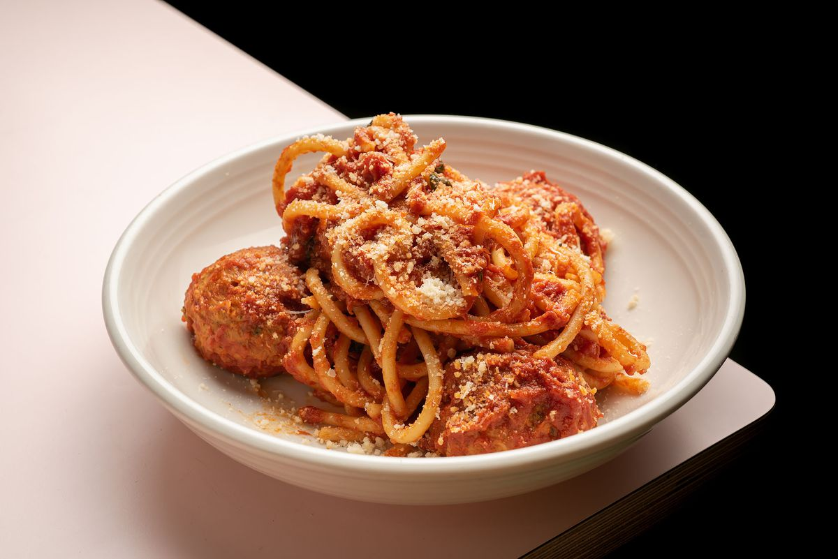 A plate of thick spaghetti and meatballs in a round bowl.