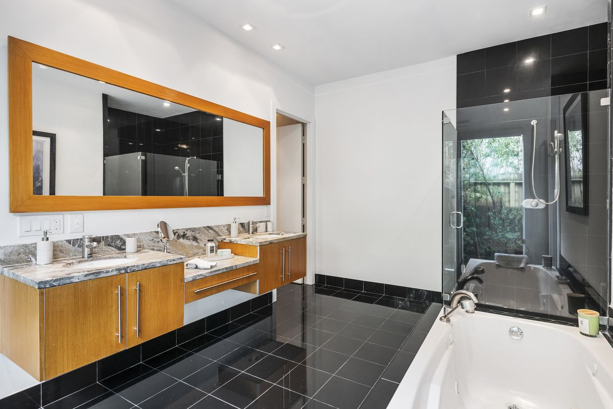 A bathroom with double sink, tub, black tile, and stand-up shower.